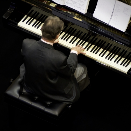 senior man playing on a grand piano, top view