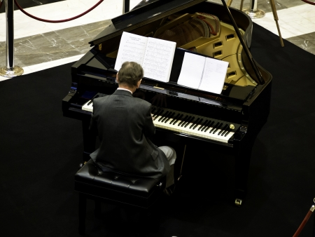 senior man playing on a grand piano, from back view