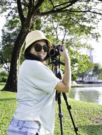 shootting: Beautiful smiling asian girl with camera on nature   Stock Photo