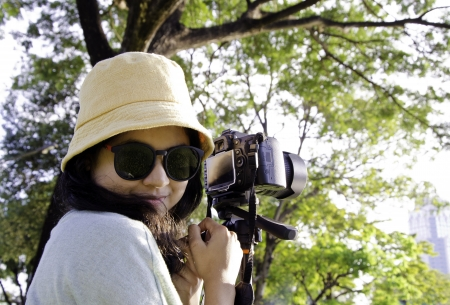 shootting: Beautiful smiling girl with camera on nature