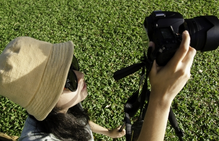 Asian girl taking photos by professional digital camera in park photo