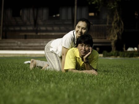 Portrait of a happy family lying on the grass in a park.  photo