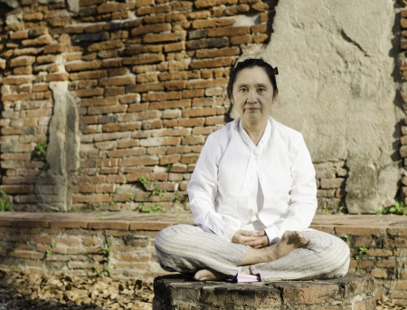 Buddhist woman meditating against ancient temple Stock Photo - 18261266