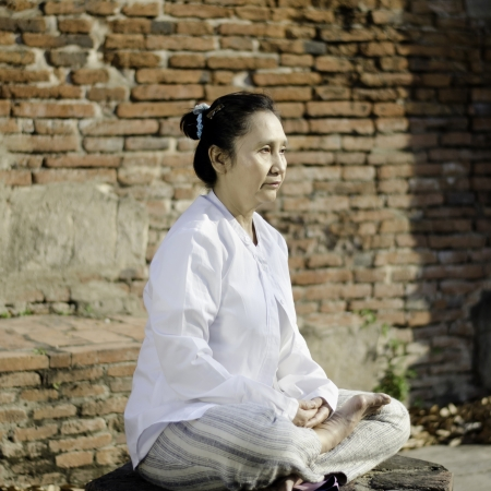 ancient yoga: Asian woman meditating yoga in ancient buddhist temple