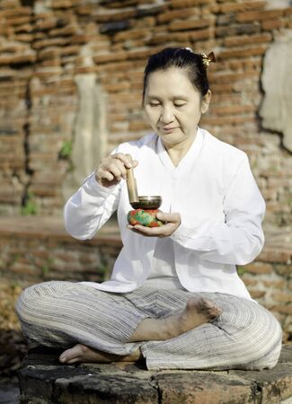Asian woman playing a tibetan bowl, traditionally used to aid meditation in Buddhist cultures.  photo