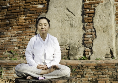 Buddhist woman meditating against ancient temple Stock Photo - 18411630