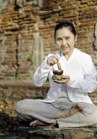 Woman playing a tibetan bowl,  traditionally used to aid meditation in Buddhist cultures.  Stock Photo - 18411632
