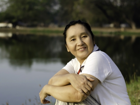 Portrait of happy asian woman in the park photo