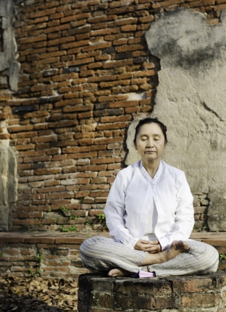 Buddhist woman meditating against ancient temple Stock Photo - 18539300