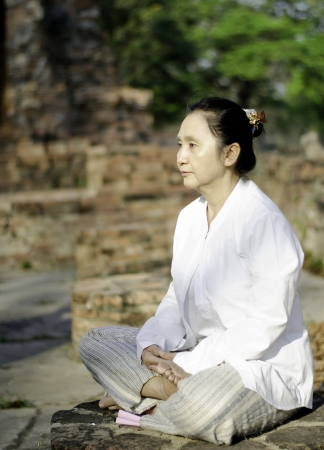 Buddhist woman meditating in ancient temple Stock Photo - 18539299