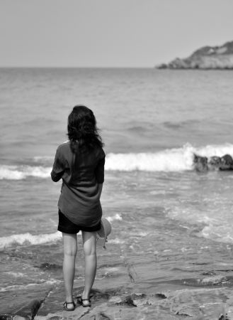 introspective: Lonely young woman on the beach, in black and white