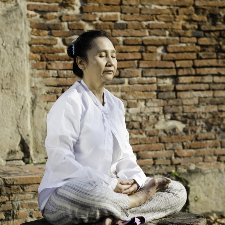 Buddhist woman meditating against ancient temple Stock Photo - 18631540