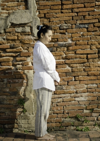Buddhist woman standing meditating against ancient temple Stock Photo - 18631543