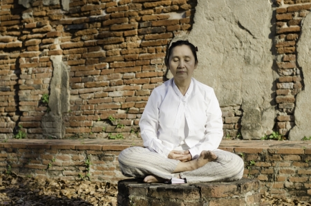 Buddhist woman meditating against ancient temple Stock Photo - 18809952