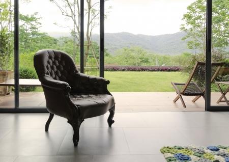 自然の背景と部屋でヴィンテージの革張りの椅子