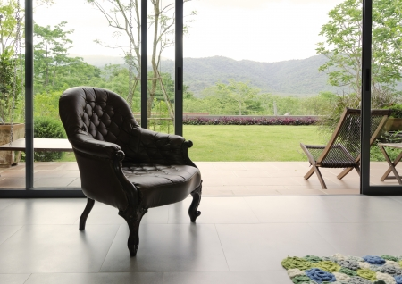 view of a comfortable bedroom: Vintage leather chair in room with nature background Editorial