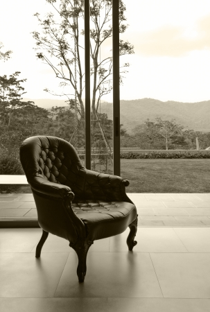 Vintage leather chair in room with nature background, sepia processed
