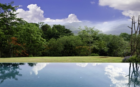 Cloud reflections on the infinity pool with beautiful landscape background photo