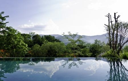 インフィニティ プールで雲や木の反射 写真素材