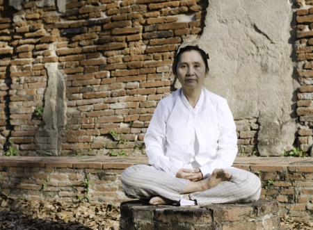 Buddhist woman meditating against ancient temple Stock Photo - 19804830