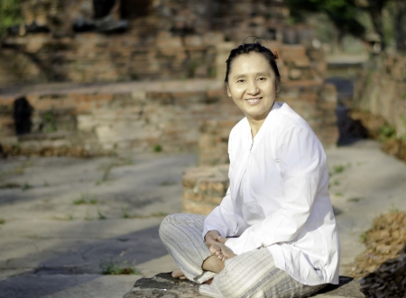 Smiling woman meditating in ancient buddhist temple  Stock Photo - 19804812