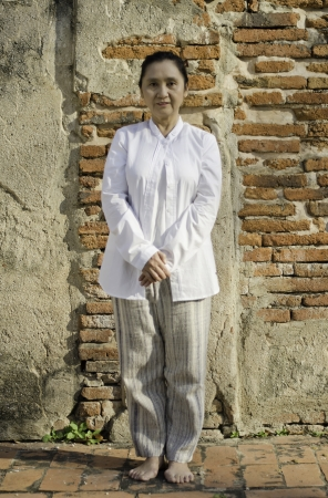 Asian woman standing meditating against ancient temple Stock Photo - 19804807