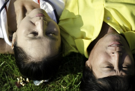 Closeup of senior couple lying on the grass with heads together  photo