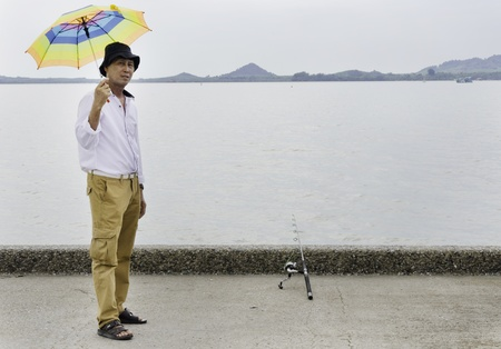 Senior fisherman catches a fish in the sea photo