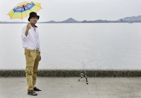 Senior fisherman catches a fish in the sea Stock Photo - 19804808