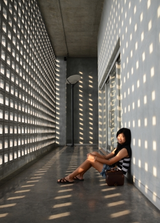 Asian girl sitting on corridor floor, dramatic interior photo