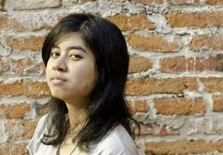 pretentious: Pretentious asian girl over brick wall Stock Photo