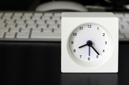 White clock, keyboard, business table in the office  photo