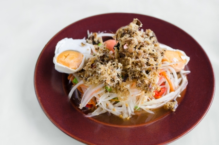 papaya salad with crisp fried catfish and salted egg, delicious thai food photo