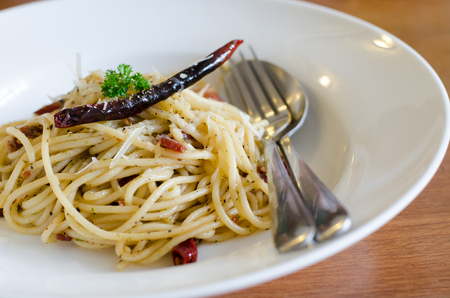 Spaghetti with ham , bacon, chilli and basil in white plate  photo