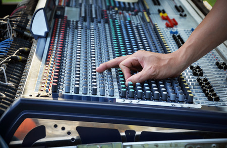 Sound engineer works with sound mixer, hands close-up  photo