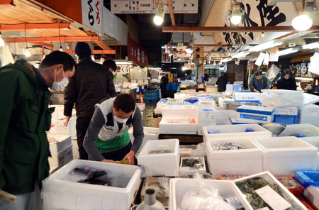 TOKYO - NOV 26  Seafood vendors at the Tsukiji Wholesale Seafood and Fish Market in Tokyo Japan on November 26, 2013  Tsukiji Market is the biggest wholesale fish and seafood market in the world