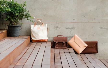 グランジ コンクリート背景にファッション革製バッグ
