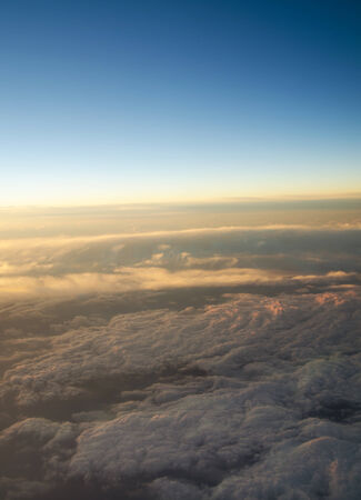 Aerial view of a cloudy sunrise while flying above the clouds   photo