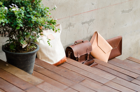 Fashion Leather Bags on Wood Step Floor, Grunge Concrete Background photo