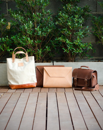 Fashion Leather Bags on Wood Floor, Nature Background photo