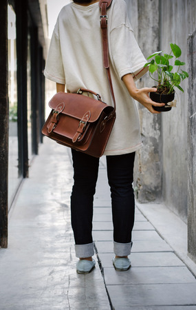 Woman with brown leather bag and hold the plant photo