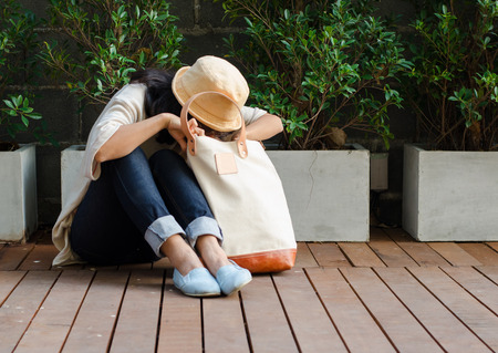 Young woman finding something in a canvas bag, Outdoor portrait