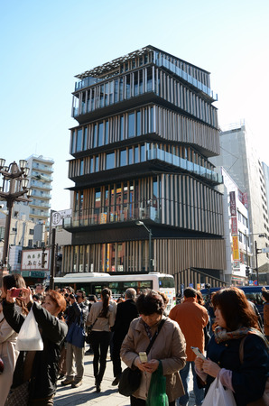 accommodate: TOKYO -NOV 21  Unidentified tourists around Asakusa Culture Tourist Center on November 21, 2013 in Tokyo,Japan, the building was required to accommodate plural programs such as tourist information center, conference room, multi-purpose hall and an exhibit