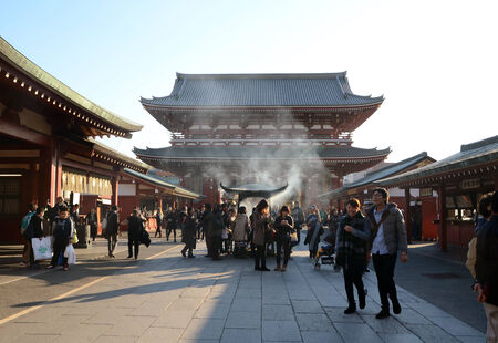 TOKYO, JAPAN - NOV 21  Buddhists gather around a fire to light incense and pray at Sensoji Temple on November 21, 2013 in Tokyo, Japan