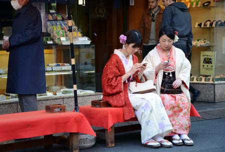 TOKYO, JAPAN - NOVEMBER 21, 2013  Young Japanese women wearing a traditional dress called Kimono for cherry  Sakura  blossom viewing at Asakusa area in Tokyo on November 21, 2013