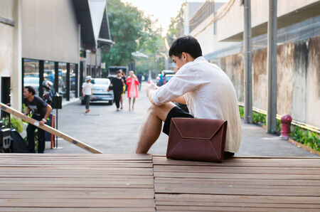 Asian man with leather bag on wooden deck photo