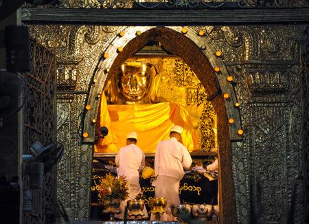 MANDALAY, MYANMAR - OCTOBER 9  The ritual of daily face washing Mahamuni Buddha at Mahamuni pagoda on October 9, 2013 in Mandalay, Myanmar  This ritual commences every morning at 4 am or 4 30 am