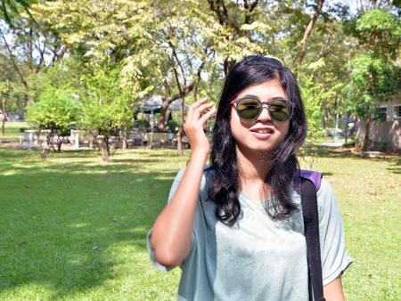 naughty woman: Young naughty woman looking at camera through sunglasses Stock Photo