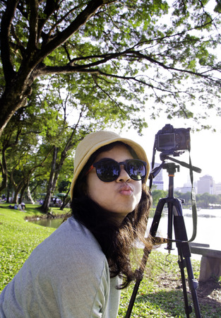 Young naughty asian girl with camera at public park