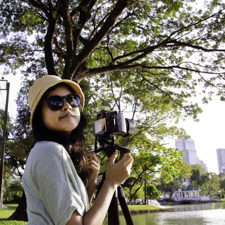 Asian girl with camera in public park